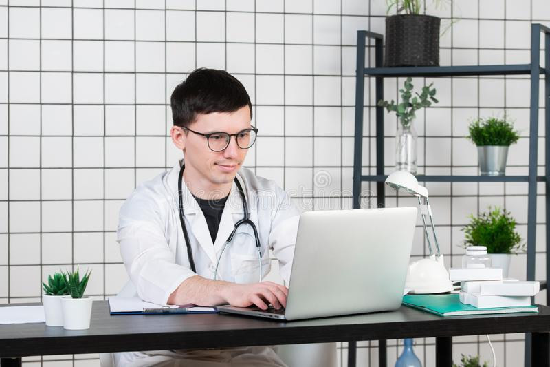 Врачуйте входя в терпеливые примечания на компьтер-книжке в хирургии стоковые изображения