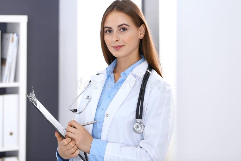 Врачуйте женщину заполняя вверх по медицинской форме пока стоящ близко окно в офисе больницы Счастливый врач на работе Медицина стоковая фотография