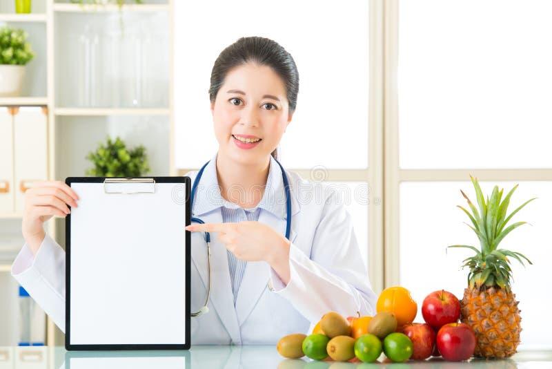 Врачуйте диетолога с плодоовощами и держать пустую доску сзажимом для бумаги стоковая фотография