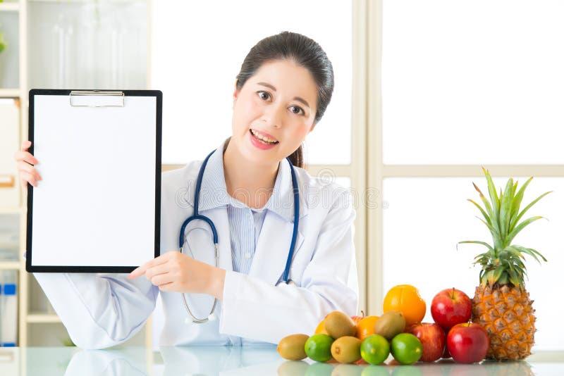 Врачуйте диетолога с плодоовощами и держать пустую доску сзажимом для бумаги стоковое изображение