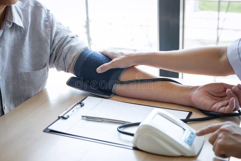 Врачуйте используя измеряя кровяное давление проверяя пациента с рассматривать, представляющ симптом результатов и порекомендуйте стоковая фотография rf