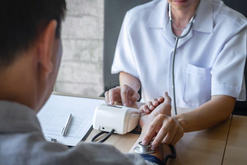 Врачуйте используя измеряя кровяное давление проверяя пациента с рассматривать, представляющ симптом результатов и порекомендуйте стоковые фото
