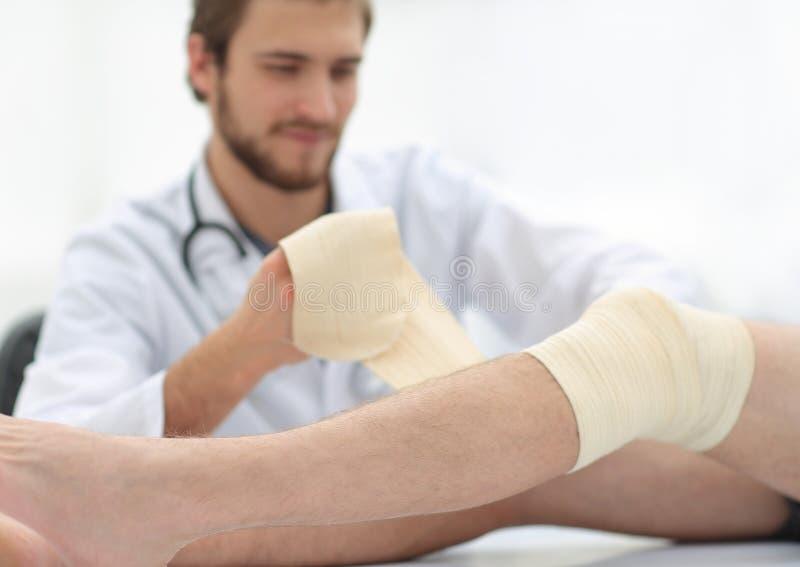 Врачуйте перевязывать рану на ноге пациента стоковое изображение rf