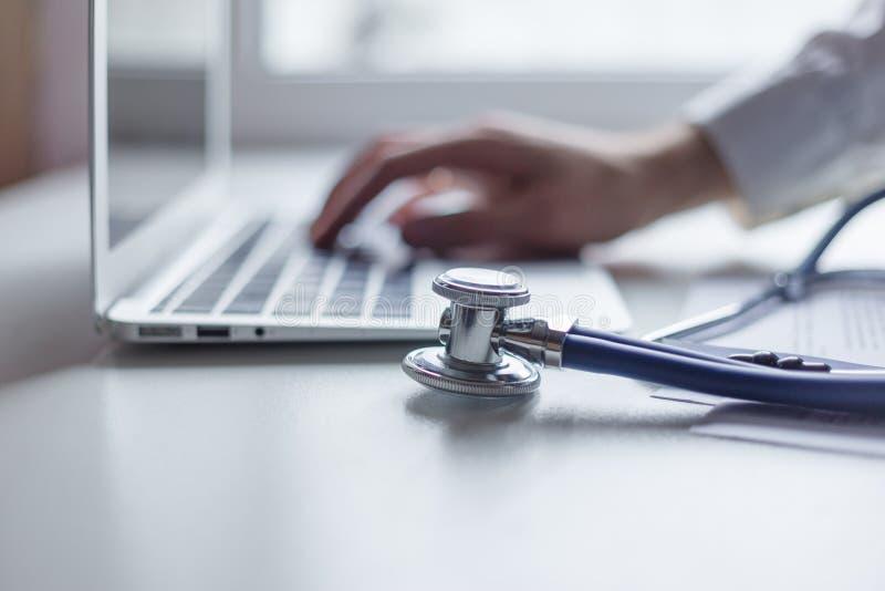 Врачуйте работу с портативным компьютером в медицинском офисе места для работы Фокус на стетоскопе стоковая фотография