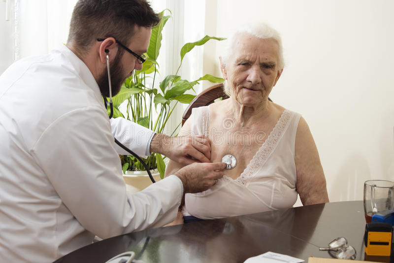 Врачуйте рассматривать старуху с стетоскопом в офисе ` s доктора стоковое изображение