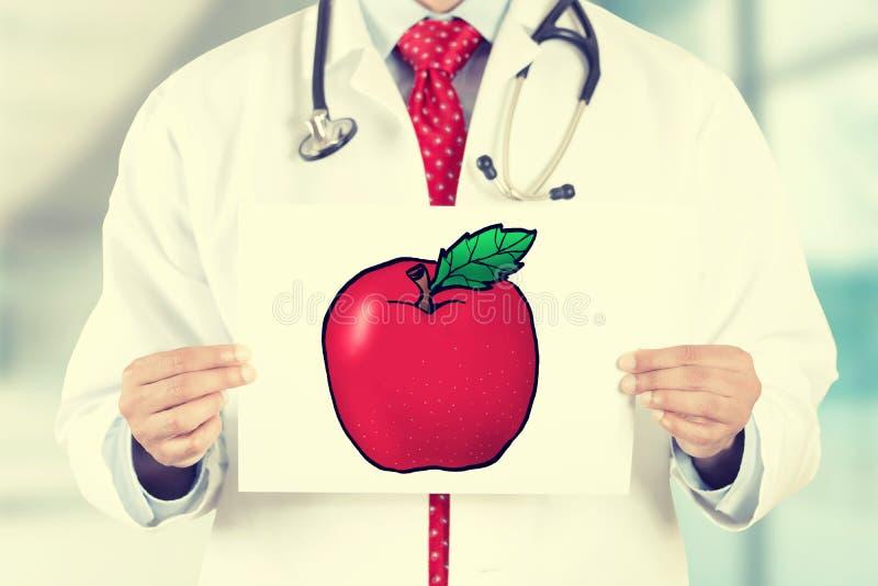 Врачуйте руки держа белую карточку с красным знаком яблока стоковая фотография rf