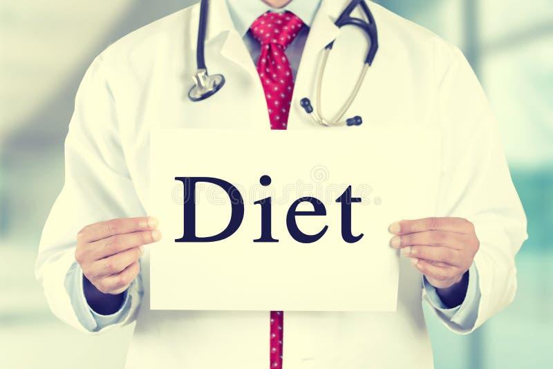 Врачуйте руки держа белый знак карточки с текстовым сообщением диеты стоковые фотографии rf