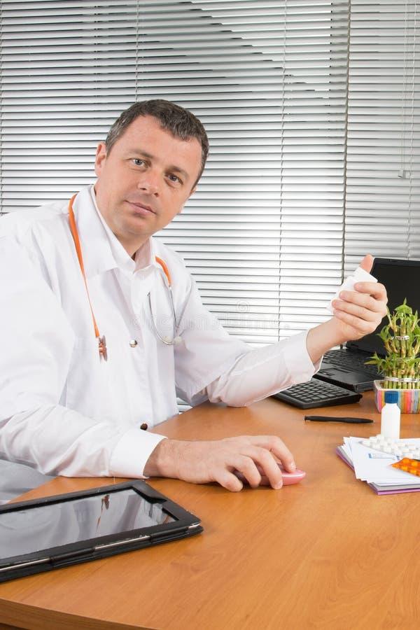 Врачуйте сидеть на столе смотря камеру в медицинском офисе стоковое фото