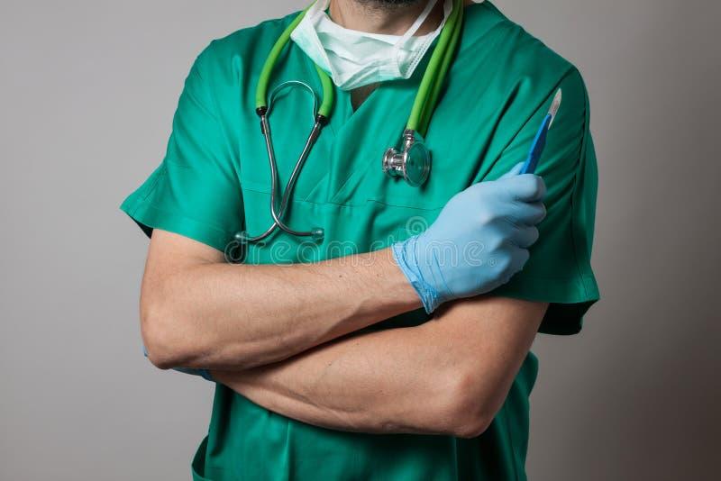 Врач держа хирургический нож стоковая фотография
