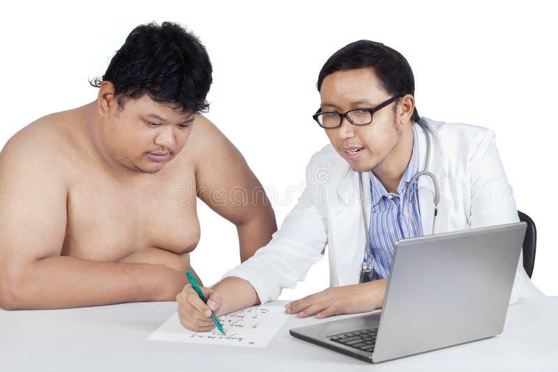 Врач делает рецепт к его пациенту стоковое изображение