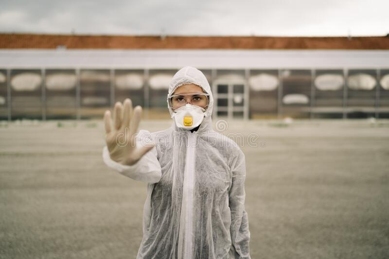 Врач-коронавирусный врач перед больницей в изоляторе Медик 'Ковид-19' с защитным снаряжением Знак остановки руки Остановить корон стоковое фото
