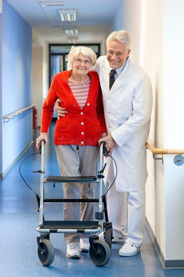 Врач помогая старшей женщине в ходоке стоковые изображения rf