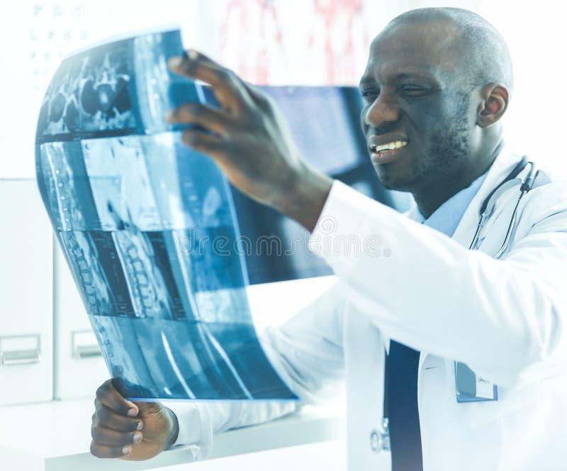 Врач портрета молодой африканский держа рентгеновский снимок пациента стоковая фотография