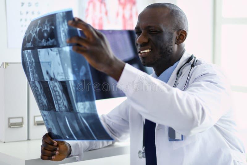 Врач портрета молодой африканский держа терпеливый рентгеновский снимок ` s стоковые изображения