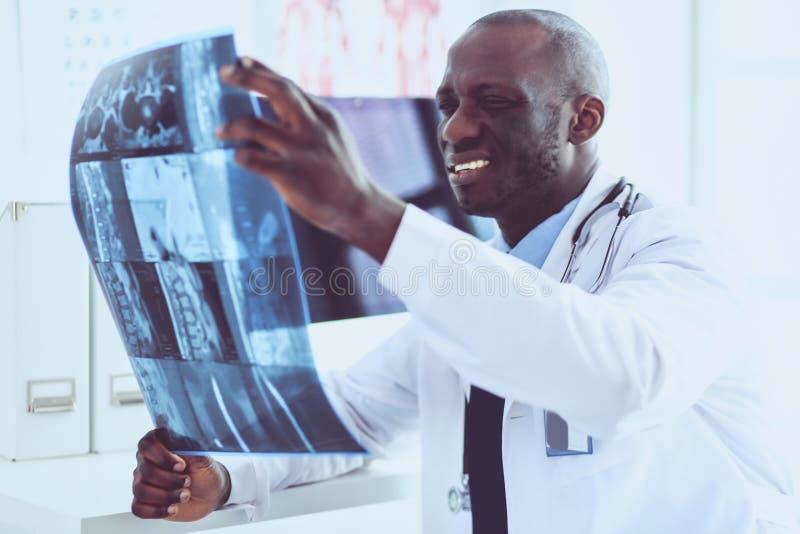 Врач портрета молодой африканский держа терпеливый рентгеновский снимок ` s стоковые фотографии rf
