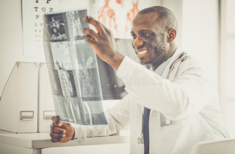 Врач портрета молодой африканский держа терпеливый рентгеновский снимок ` s стоковые фото