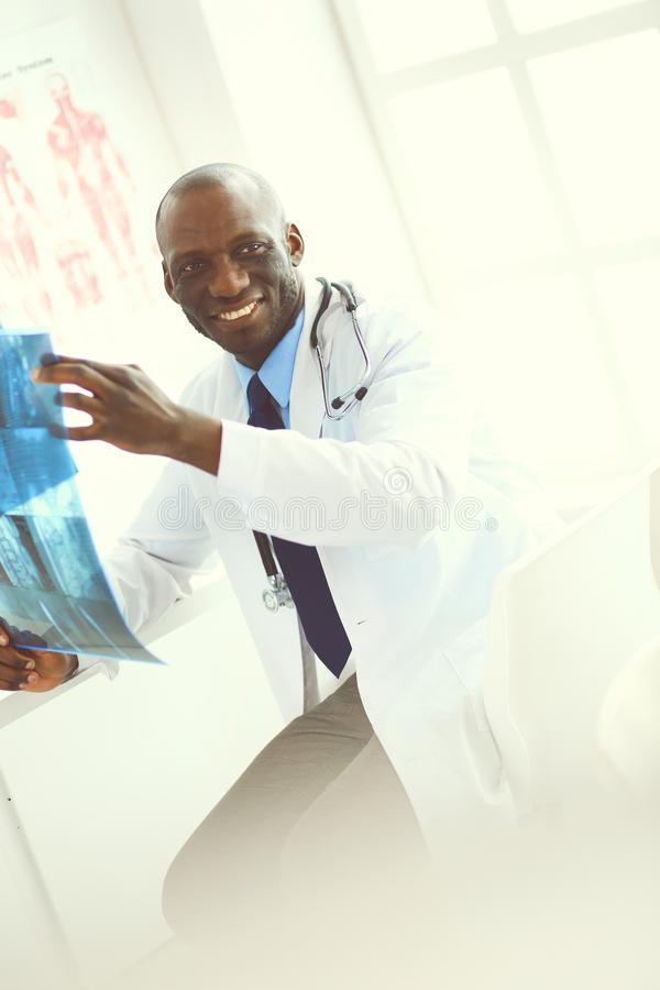 Врач портрета молодой африканский держа терпеливый рентгеновский снимок ` s стоковое фото rf