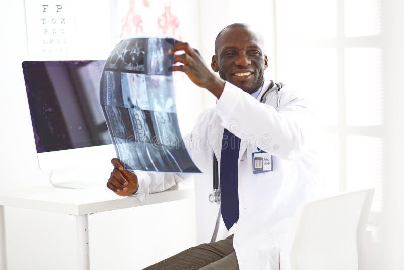 Врач портрета молодой африканский держа терпеливый рентгеновский снимок ` s стоковая фотография rf