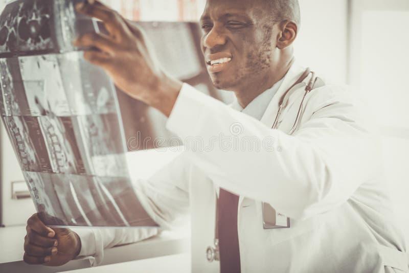 Врач портрета молодой африканский держа терпеливый рентгеновский снимок ` s стоковое фото