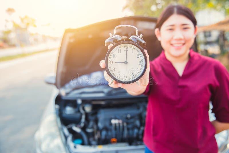 Времена к концепции проверки автомобиля: Азиатские женщины держа часы стоковая фотография