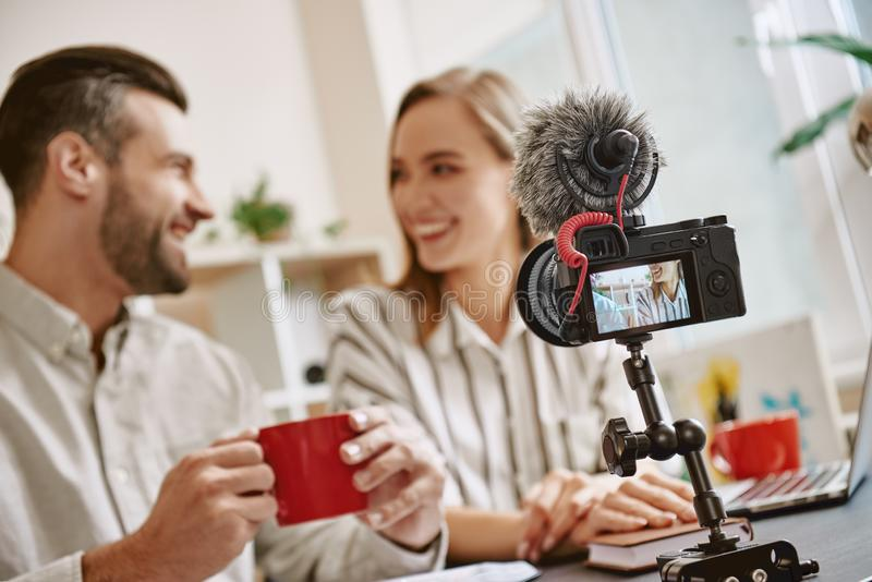 Время для пролома Молодые положительные блоггеры выпивают чай перед началом онлайн течь стоковое фото