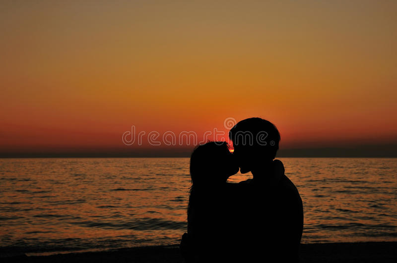 время захода солнца поцелуя пляжа романтичное стоковая фотография rf