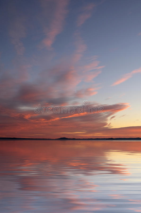 Время захода солнца над озером стоковые изображения