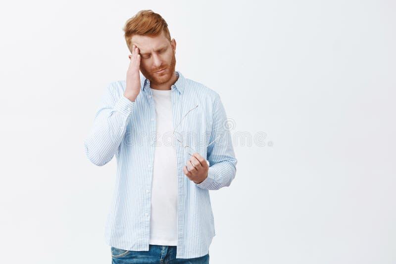 Время идет домой, очень уставший Портрет вымотанного хмурого бизнесмена redhead в случайной голубой рубашке, виске затирания, при стоковые фотографии rf