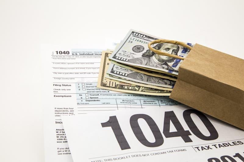 Время подоходного налога формирует предпосылку белизны денег сумки наличных денег 1040 стоковая фотография rf