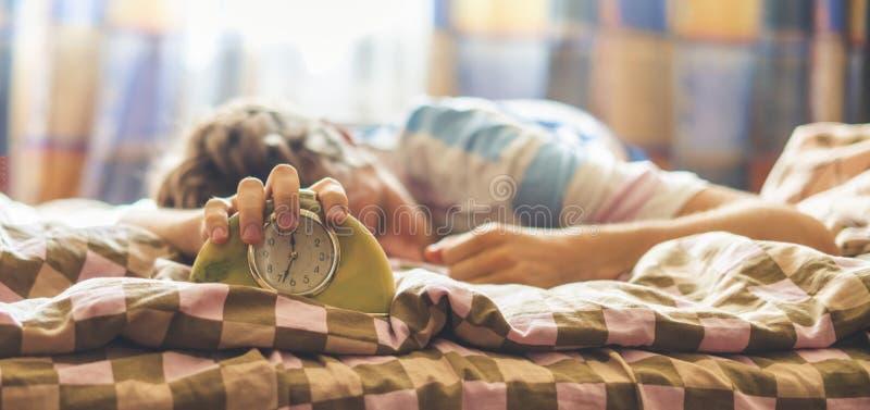 Время проспать вверх, лежать спать в человеке кровати бьет будильник в утре f стоковое фото rf