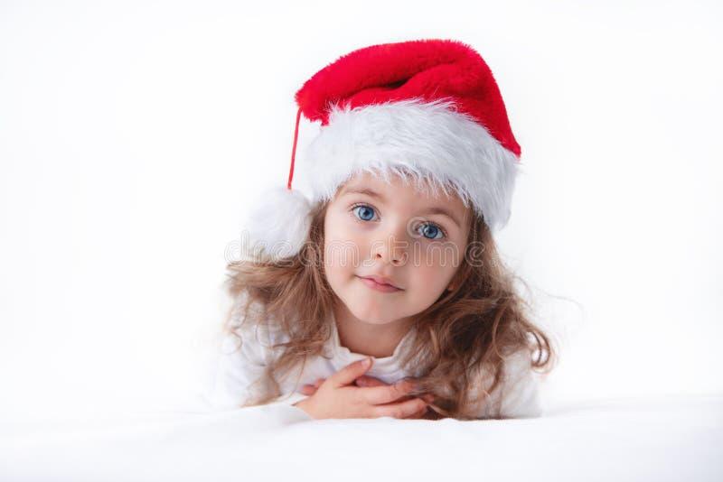 Время рождества, маленькая девочка в шляпе Санта Клауса smilling стоковая фотография rf