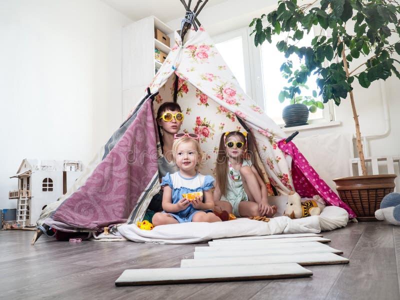 Время семьи: Мама и некоторые из детей сестер играют дома в шатре детей домодельном стоковые фото