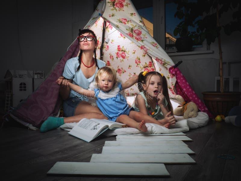 Время семьи: мать и дети сестер в темной игре дома в шатре детей домодельном стоковые фото