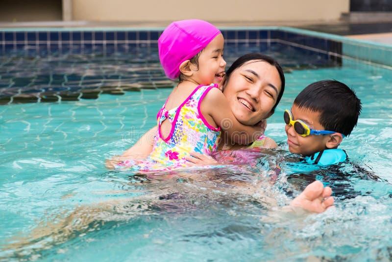 Время семьи порожное поплавать в бассейне они наслаждаются сыграть t стоковые изображения rf