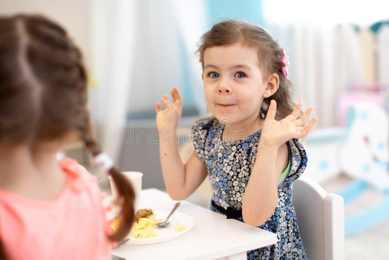 Время съесть в детском саде Маленькая девочка имеет обедающий в daycare стоковые фото