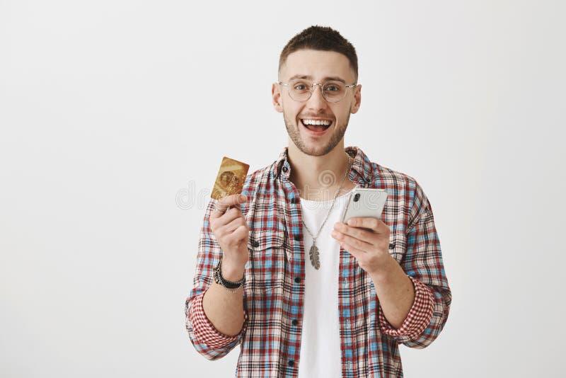 Время технологии становилось Крытая съемка удовлетворенного счастливого клиента в ультрамодных одеждах держа smartphone и кредит стоковая фотография rf
