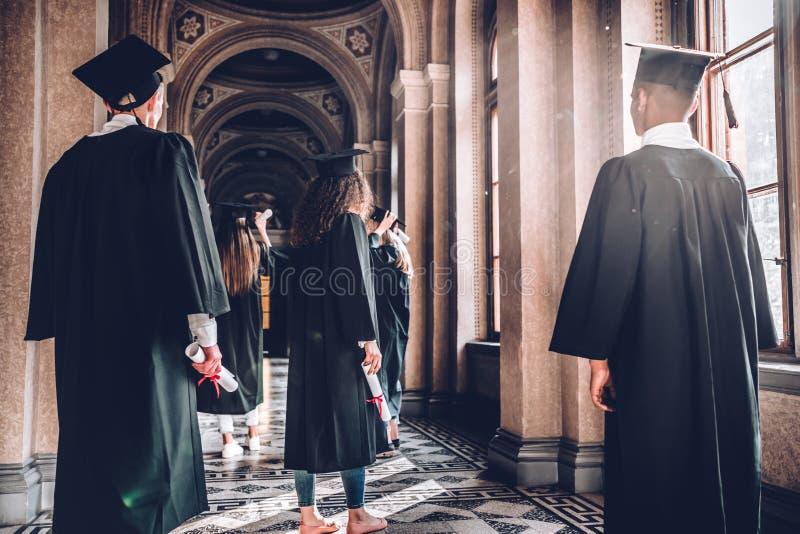 Время шагнуть в новый мир Вид сзади снял группы в составе студенты стоя в зале университета стоковые изображения rf