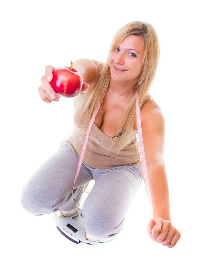 Время для уменьшения диеты. Женщина на ленте яблока масштабов измеряя стоковые изображения