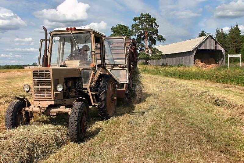 Время Haymaking, русский трактор фермы с круглым baler жмет h стоковые фотографии rf