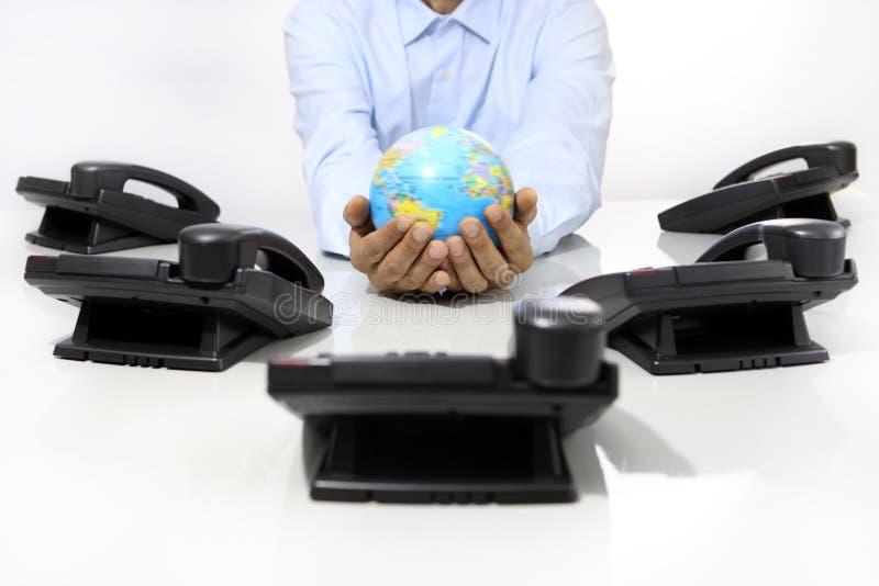 Вручает глобус с телефонами офиса на столе, глобальном международном маленьком глотке стоковое изображение rf