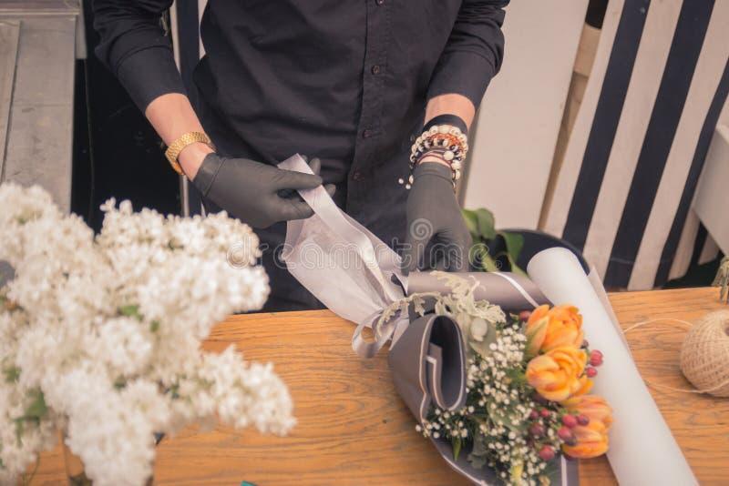 Вручает крупный план, деятельность флориста, делая аранжировать букет цветка стоковое изображение