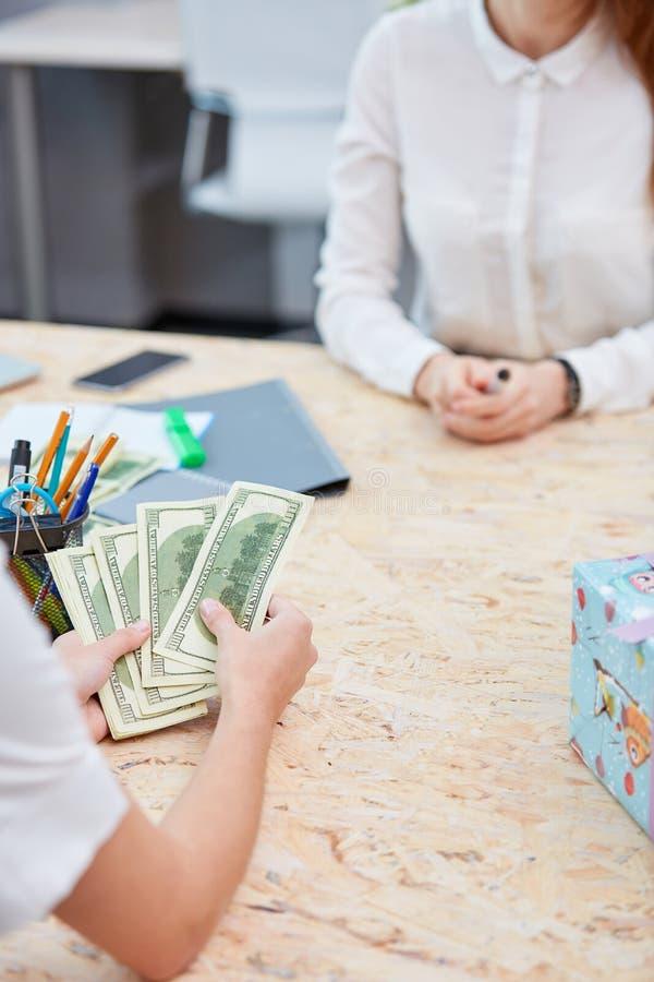 Вручает подсчитывать деньги пока консультант ждет конец-вверх стоковое изображение