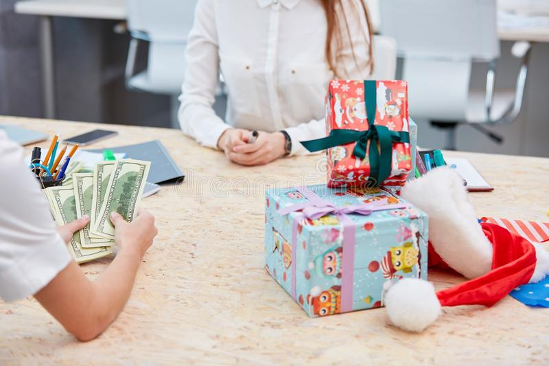 Вручает подсчитывать деньги пока консультант ждет на таблице с кучей подарков стоковые изображения