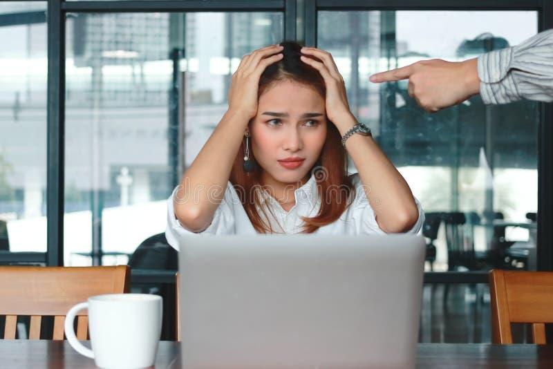 Вручите босса ` s указывая тревоженая подавленная азиатская бизнес-леди в офисе стоковая фотография