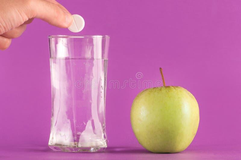Вручите бросая шипучую таблетку в стекло воды и яблоко на столе стоковое изображение