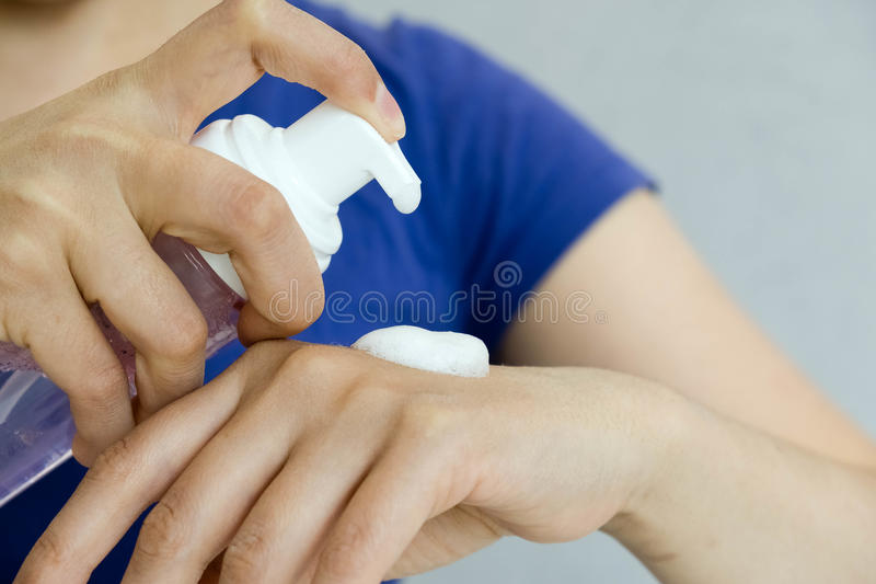 Вручите бутылку cleanser пены насоса прессы с предпосылкой ванной комнаты нерезкости концепция гигиены, мусса кладущ pomade в нал стоковое изображение rf