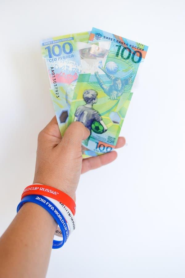 Вручите держать более новые русские деньги выданный специфически для чемпионата футбола стоковая фотография rf
