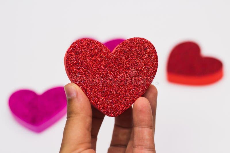 Вручите держать красное сердце яркого блеска против запачканных сердец на белой предпосылке стоковое фото