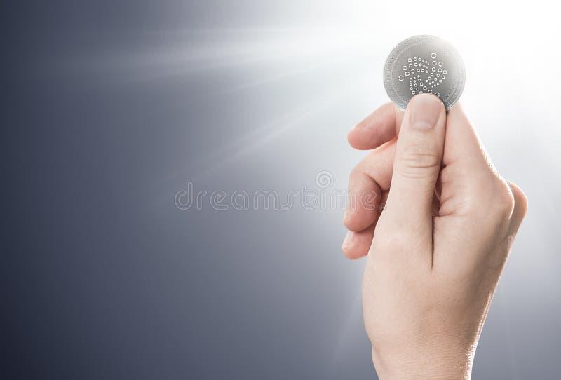 Вручите держать монетку IOTA серебра на нежно освещенной предпосылке иллюстрация штока
