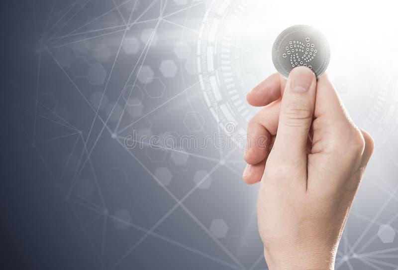Вручите держать монетку IOTA серебра на яркой предпосылке с сетью blockchain иллюстрация вектора